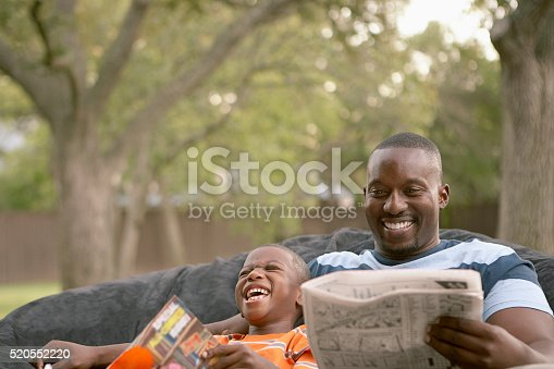 istock Father and son laughing and reading 520552220