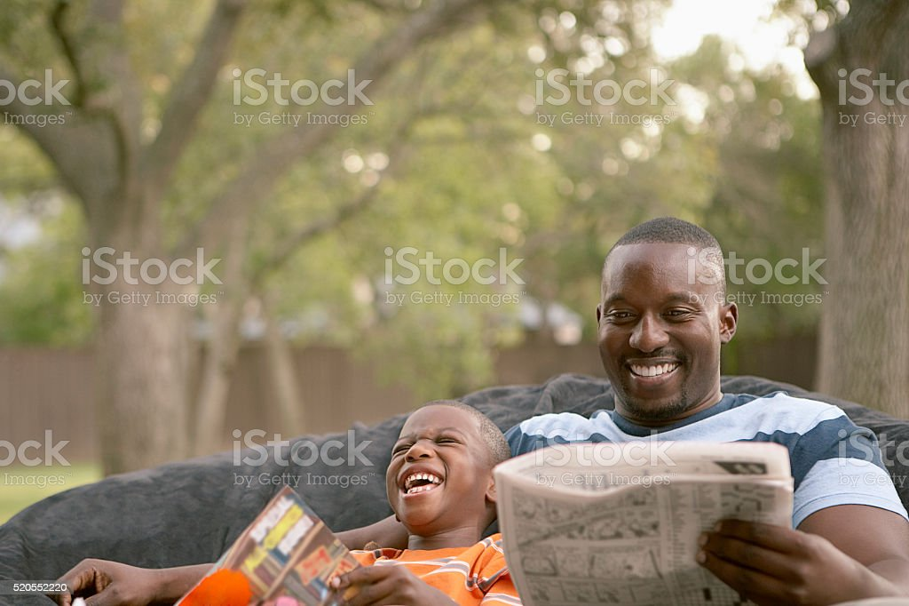 Father and son laughing and reading - foto de acervo