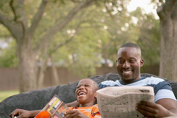 Father and son laughing and reading stock photo