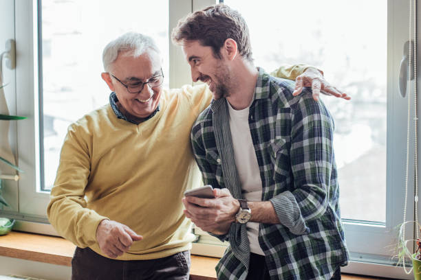 father and son laughing and using phone - son stock photos and pictures