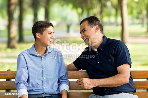 istock Father and son laughing on a bench 614045830