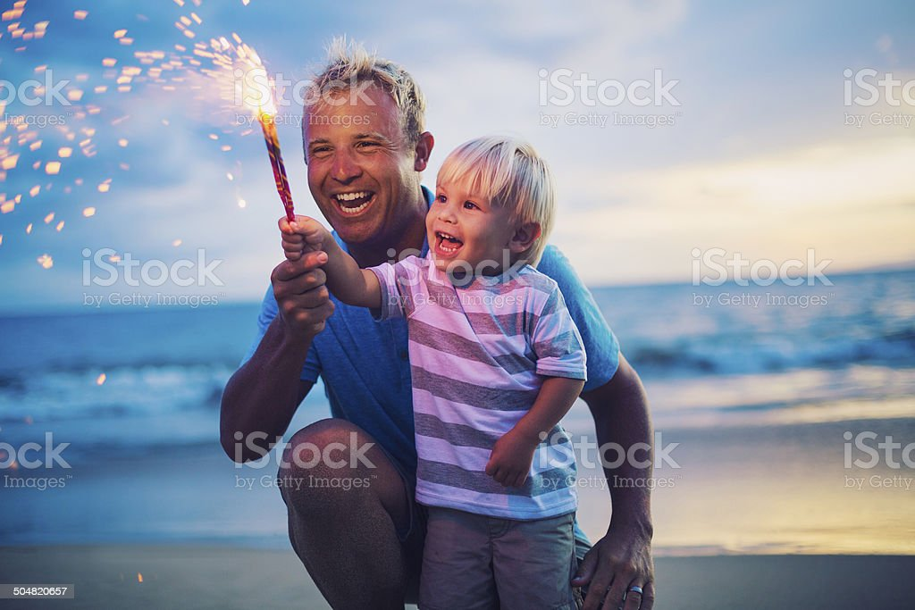 Father and son lighting fireworks stock photo