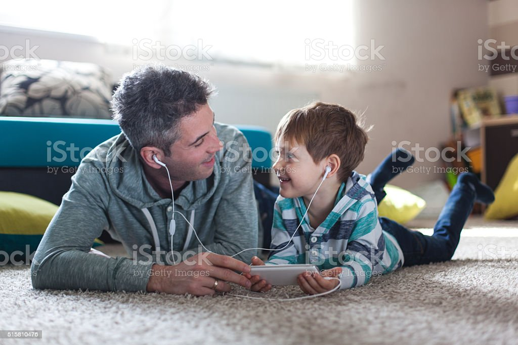 Father and son listening music stock photo
