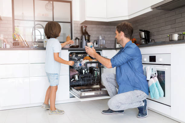 Father and son loading dishwasher together Father and son loading dishwasher together dishwasher stock pictures, royalty-free photos & images