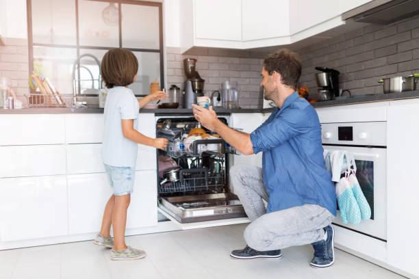 Vater und Sohn beladen Spülmaschine zusammen – Foto