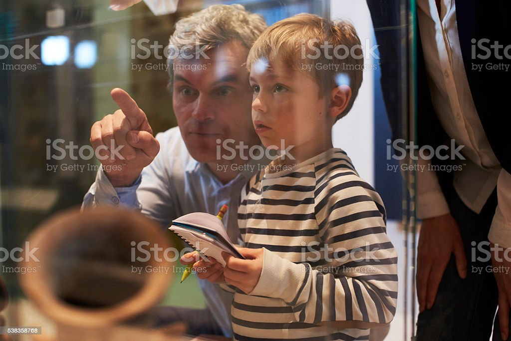 Father And Son Look At Artifacts In Case On Trip To stock photo