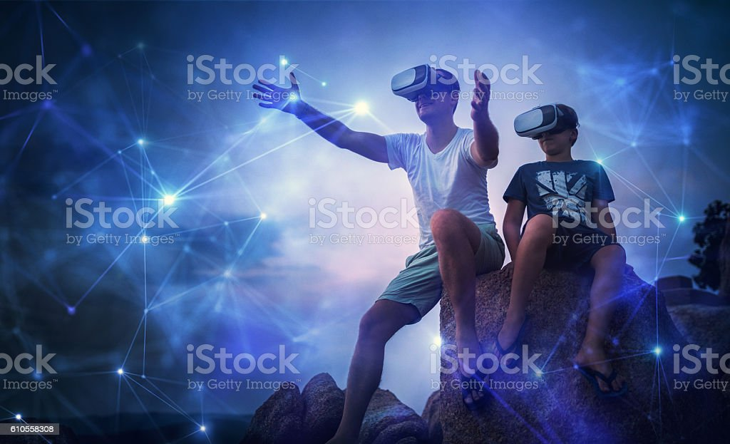 Father and son looking at futuristic network using VR glasses stock photo
