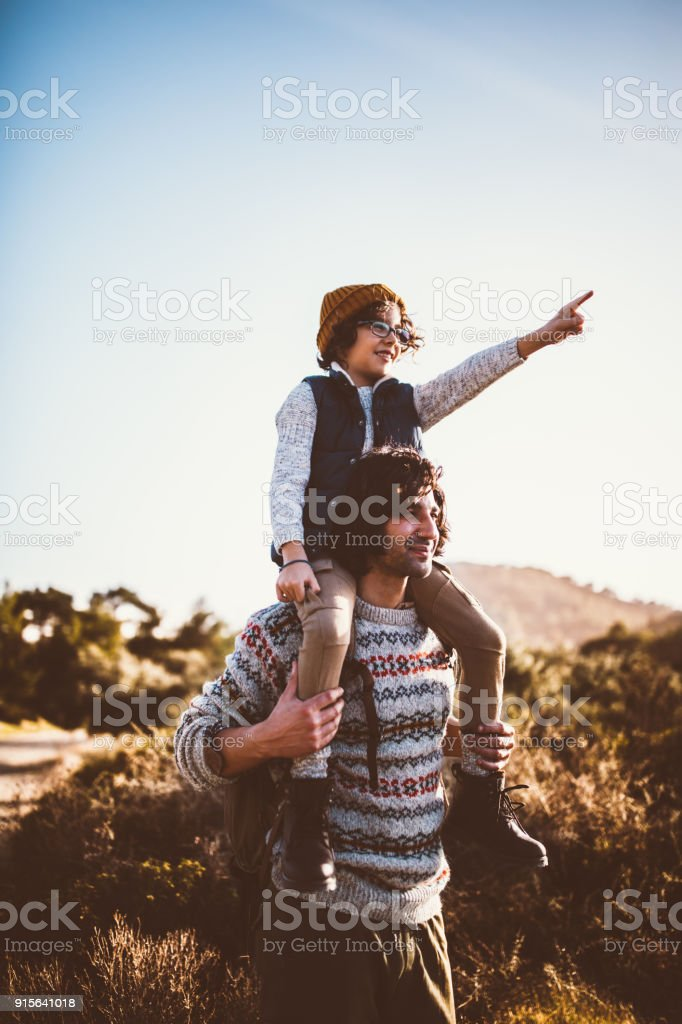 Father and son looking at mountain view on hiking trip stock photo