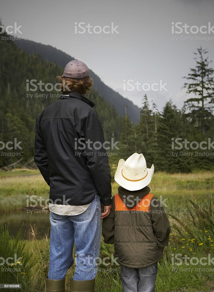 Father and son looking at river and tidal marsh royalty free stockfoto