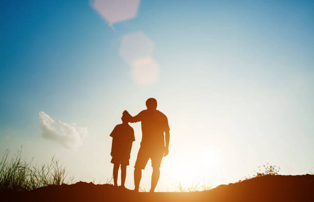Father and son looking for future,  silhouette concept stock photo