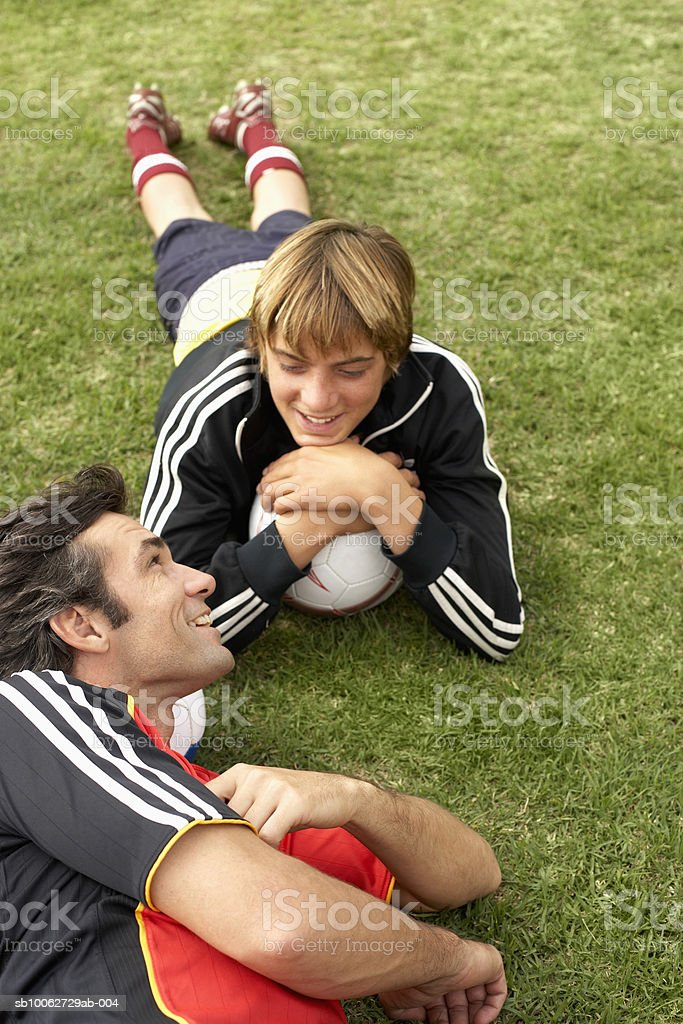 Father and son (14-15) lying on grass with football, elevated view royalty-free 스톡 사진