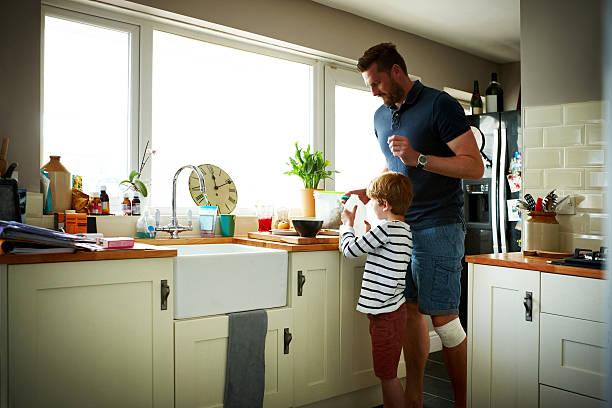 padre e hijo haciendo el desayuno - padre que se queda en casa fotografías e imágenes de stock