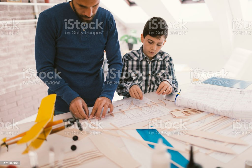 Father and son making toy plane stock photo