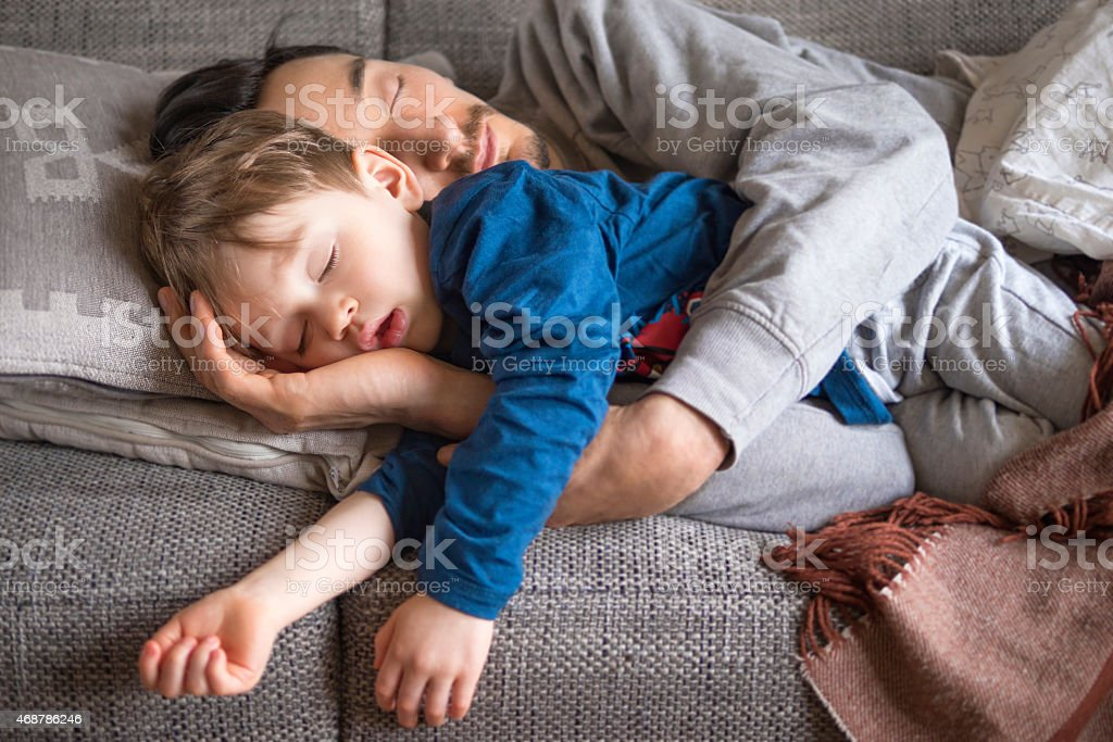 Father and son napping on the couch stock photo