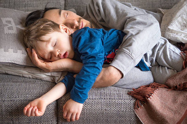 father and son napping on the couch - een dutje doen stockfoto's en -beelden