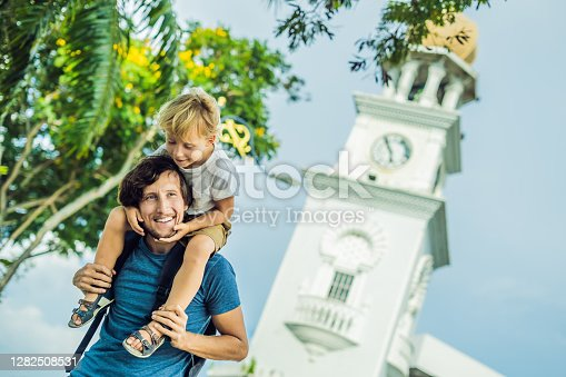 Father and son of tourists in the background of Queen Victoria Memorial clock tower, Penang.