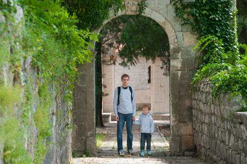 father and son on a background of ancient arch in the old garden