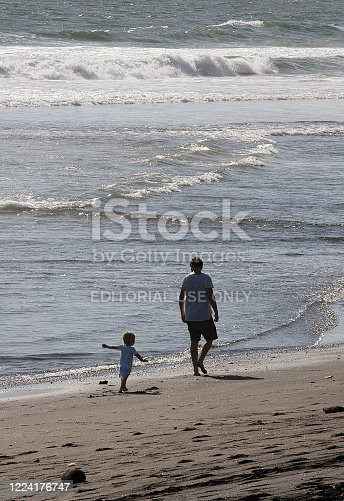 Bali, Indonesia - February 15, 2017: Colour photograph of a father and his son walking on a beach in Bali at sunset.