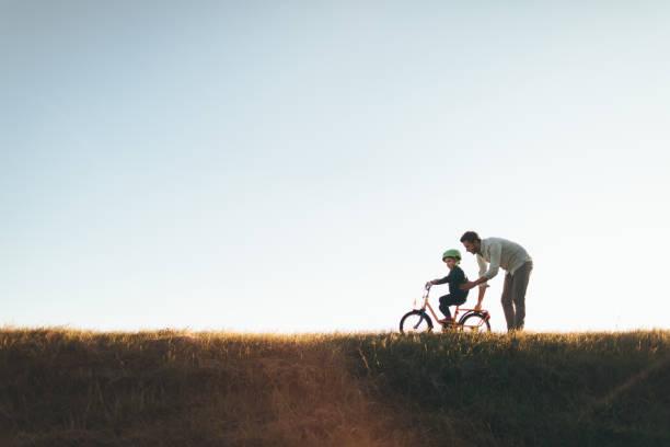 vater und sohn auf einem fahrradweg - kinderfahrrad stock-fotos und bilder