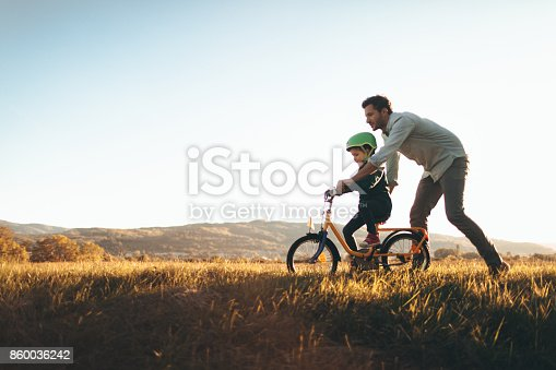 istock Father and son on a bicycle lane 860036242