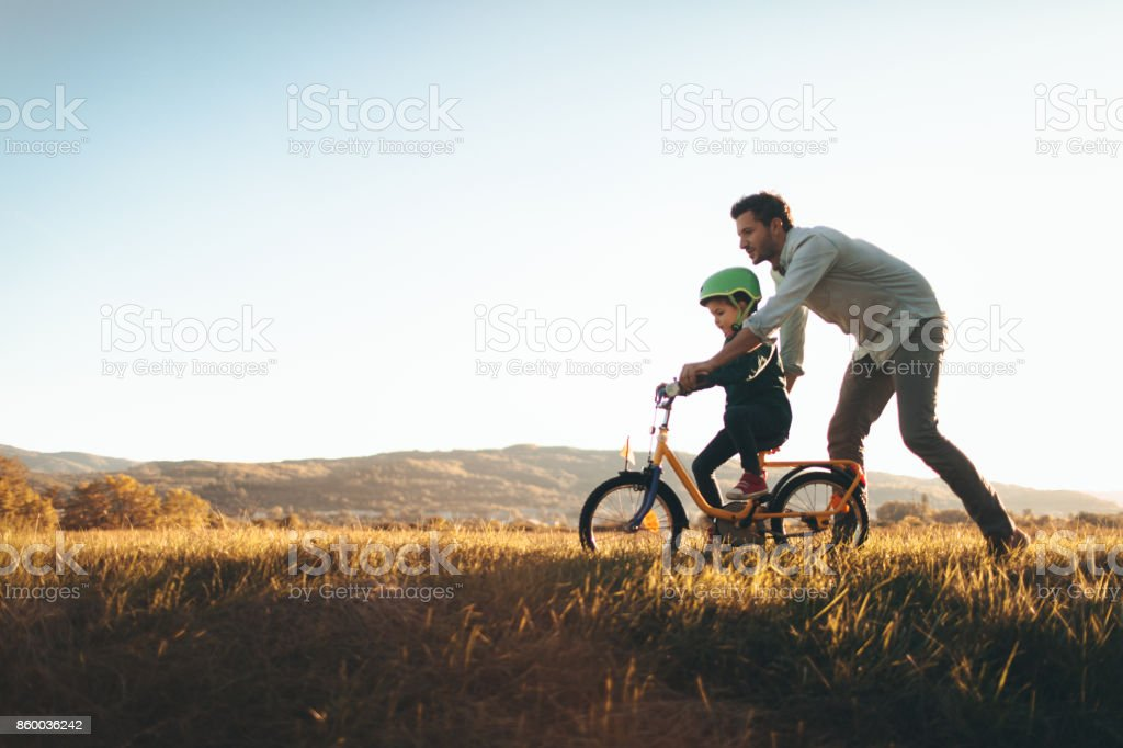 Father and son on a bicycle lane stock photo