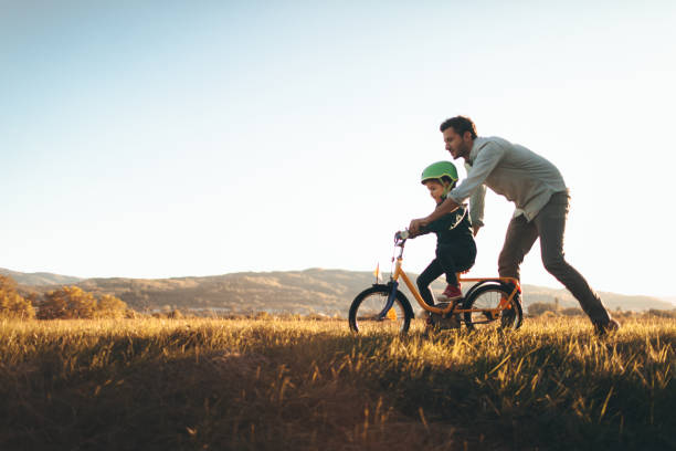father and son on a bicycle lane - cycling stock photos and pictures
