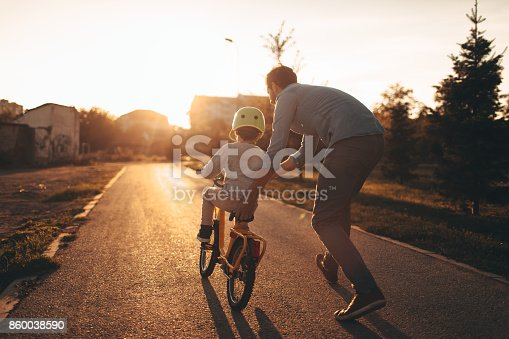 istock Father and son on a bicycle lane 860038590