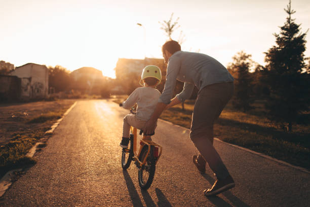 father and son on a bicycle lane - balance stock pictures, royalty-free photos & images