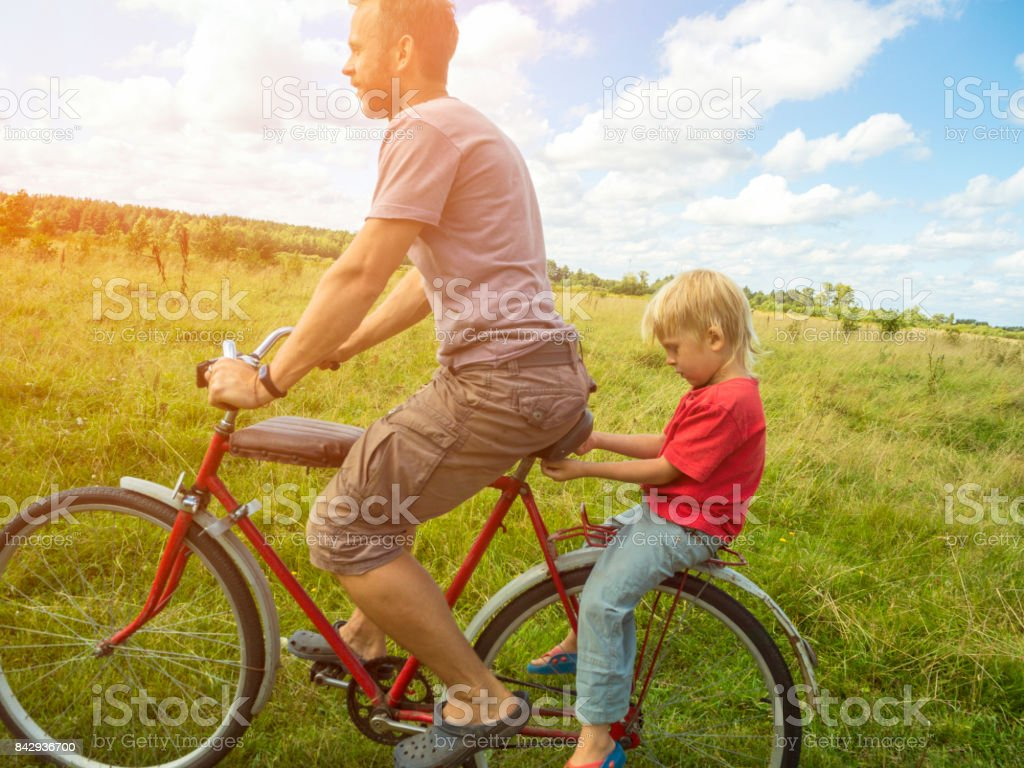 father and son on a bicycle stock photo