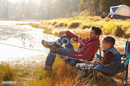 istock Father and son on a camping trip fishing by a lake 540096342
