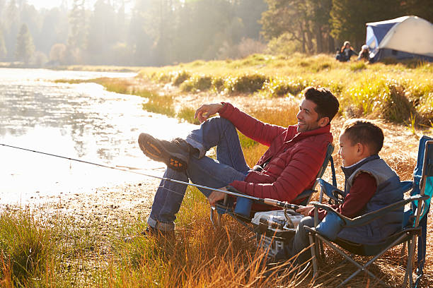 father and son on a camping trip fishing by a lake - camping stock photos and pictures
