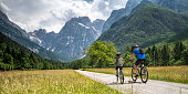 Scenic photo of a father and his son on mountain bike riding on a country road towards the mountains of the European Alps.