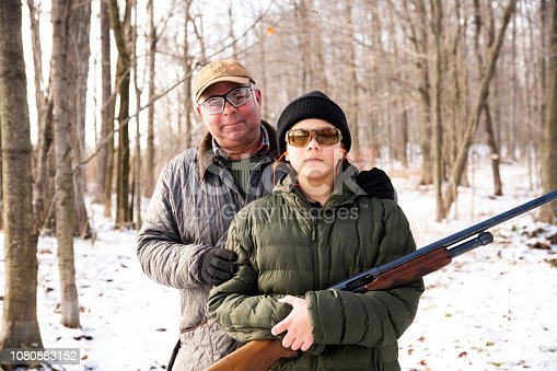 A father and son on a hunting outing in the woods on a snowy winter day.