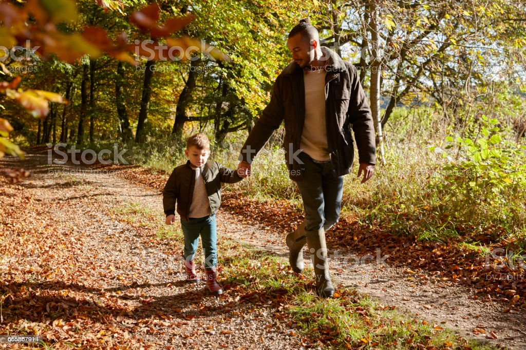Father And Son On Autumn Walk In Woodland Together stock photo