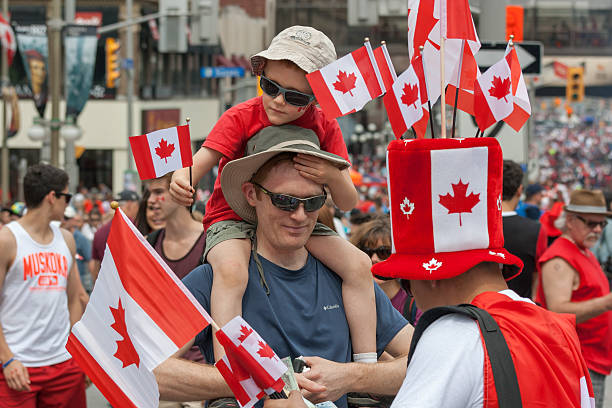 father and son on canada day - canada day stock pictures, royalty-free photos & images