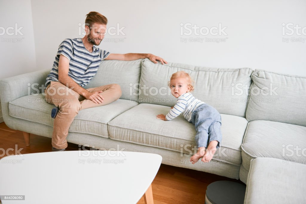 Father and son on couch. Boy crawling down stock photo