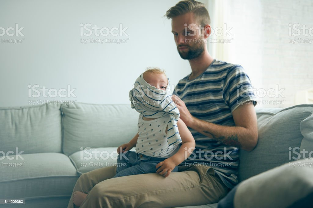 Father and son on couch. Getting dressed stock photo