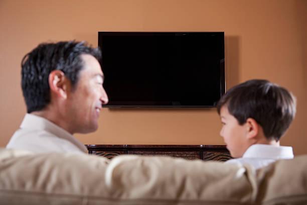 vater und sohn auf sofa fernsehen - tv wand profile stock-fotos und bilder