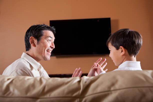 vater und sohn auf sofa mit fernseher im hintergrund. - tv wand profile stock-fotos und bilder