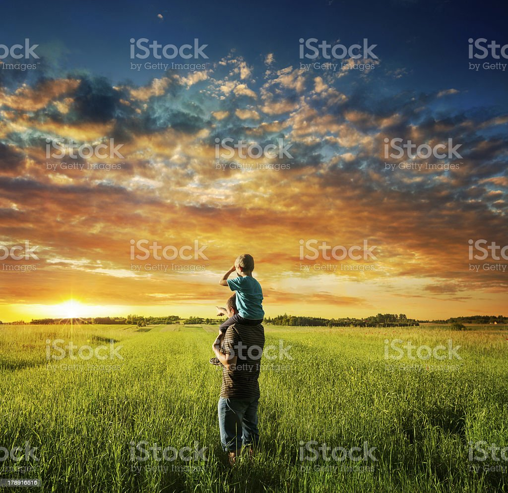 Father and son on meadow stock photo