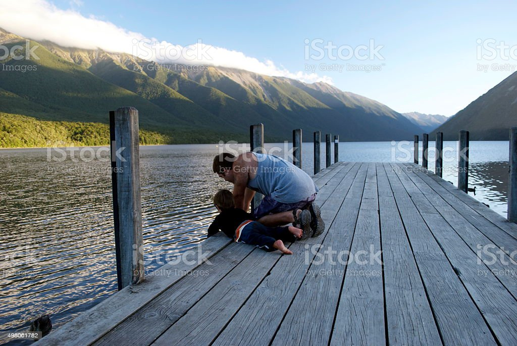 Father and Son on Pier, Nelson Lakes, New Zealand stock photo