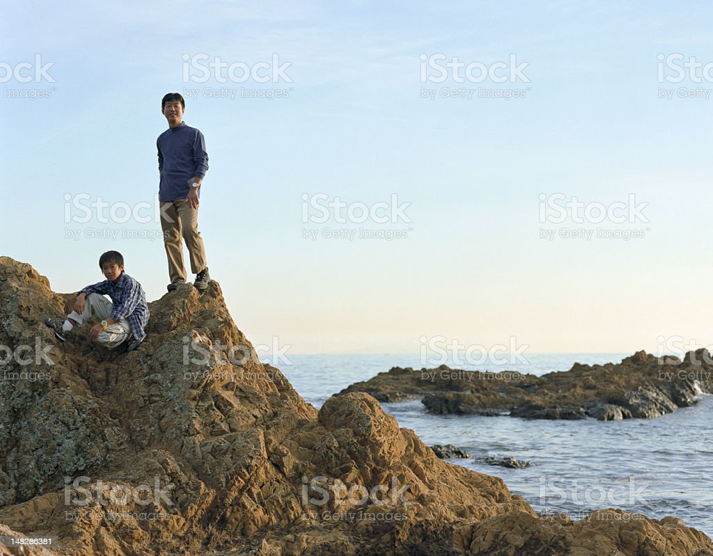 Father and son (9-11) on rock beside sea, portrait royalty-free stock photo