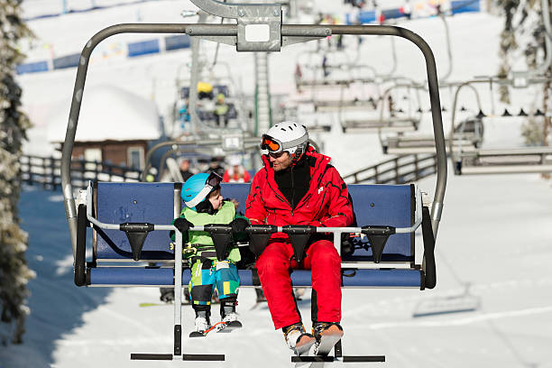 Father and son on ski lift stock photo
