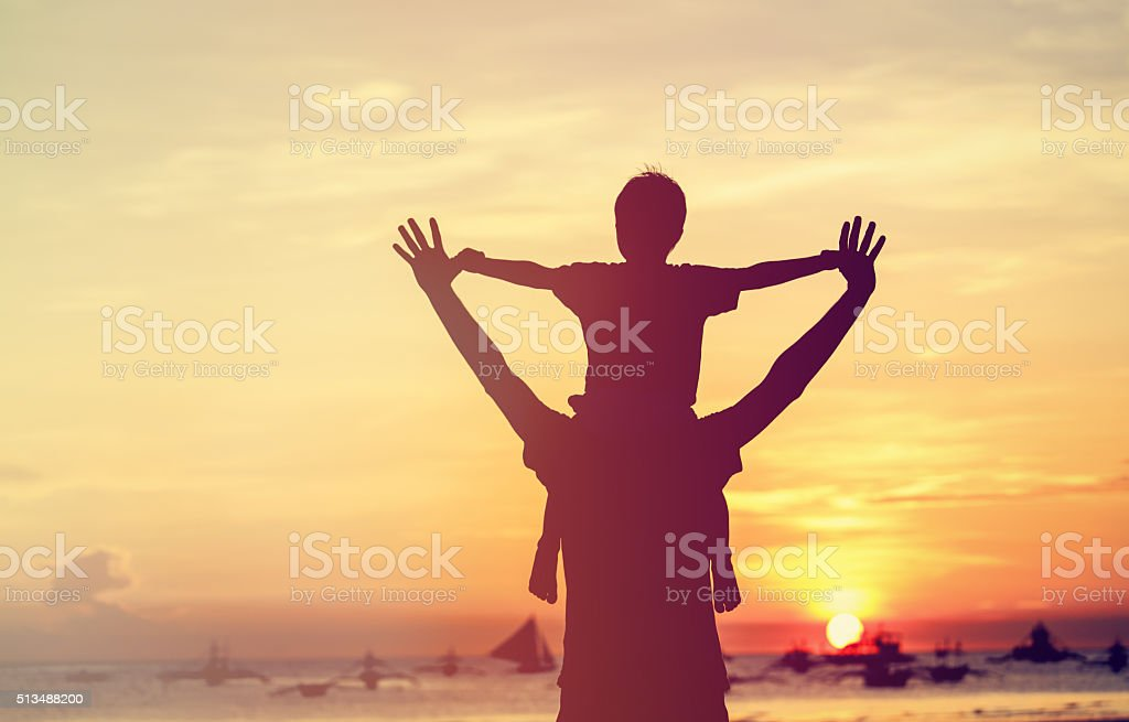 father and son on sunset beach royalty-free stock photo
