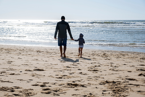 istock Father and son on the beach in sunny but cold windy weather 1174818849