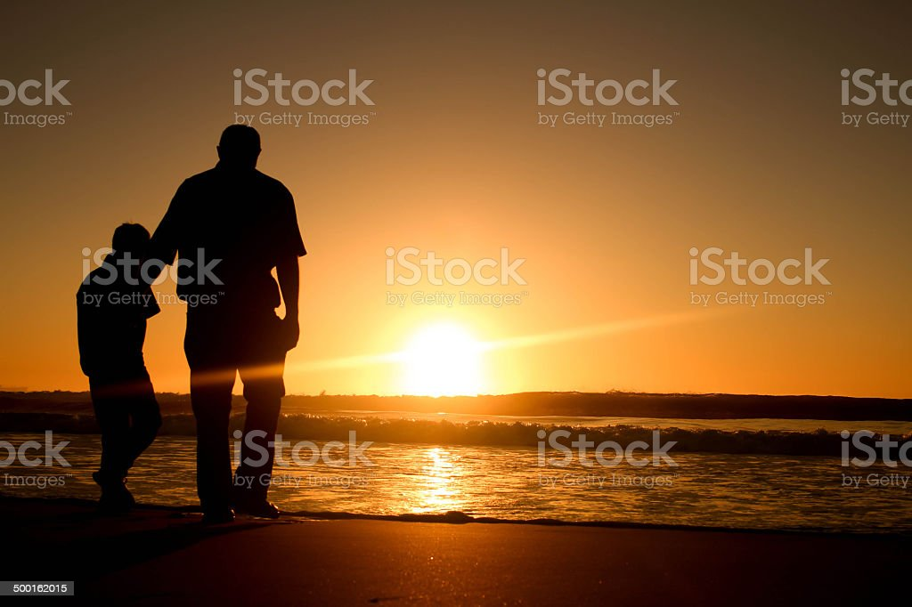Father and son on the beach with sunrise. stock photo