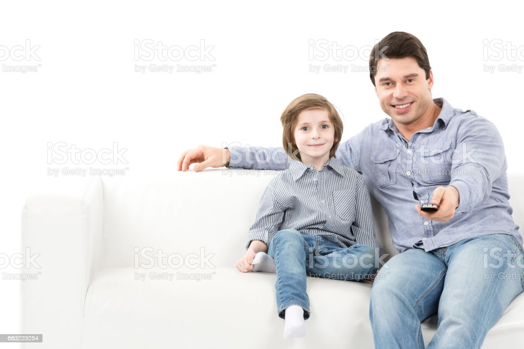 Father and son on the couch switch channels. foto de stock royalty-free