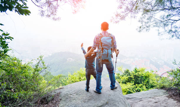 Father and son on the top of the hill stock photo