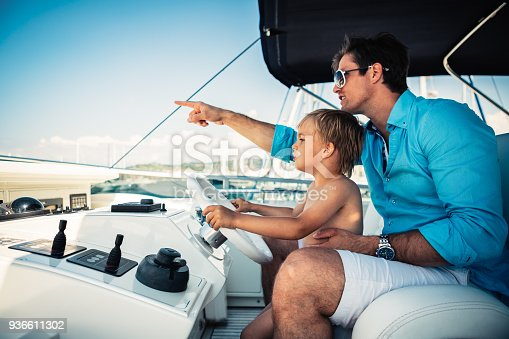 Father teaches his young son how to steer a yacht.