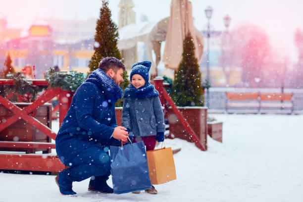 vater und sohn auf winter einkaufen in stadt, ferienzeit, geschenke kaufen - festliche babymode junge stock-fotos und bilder